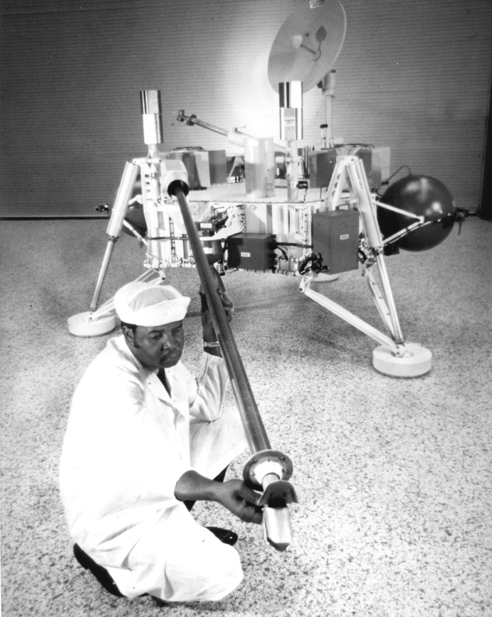 Image from NASA: A technician checking the sample arm of the Viking lander before launch