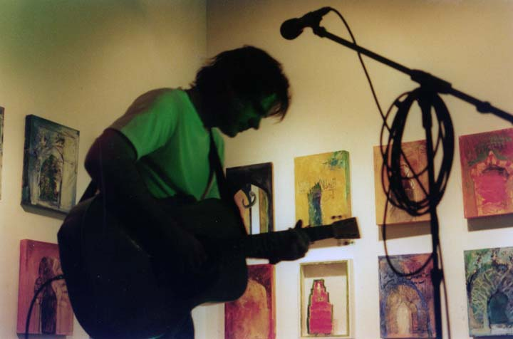 Jon Randall performing at HOME01. Margaret Tolbert paintings in the background ~ at ruby green Contemporary Arts Foundation (Nashville, 2001)