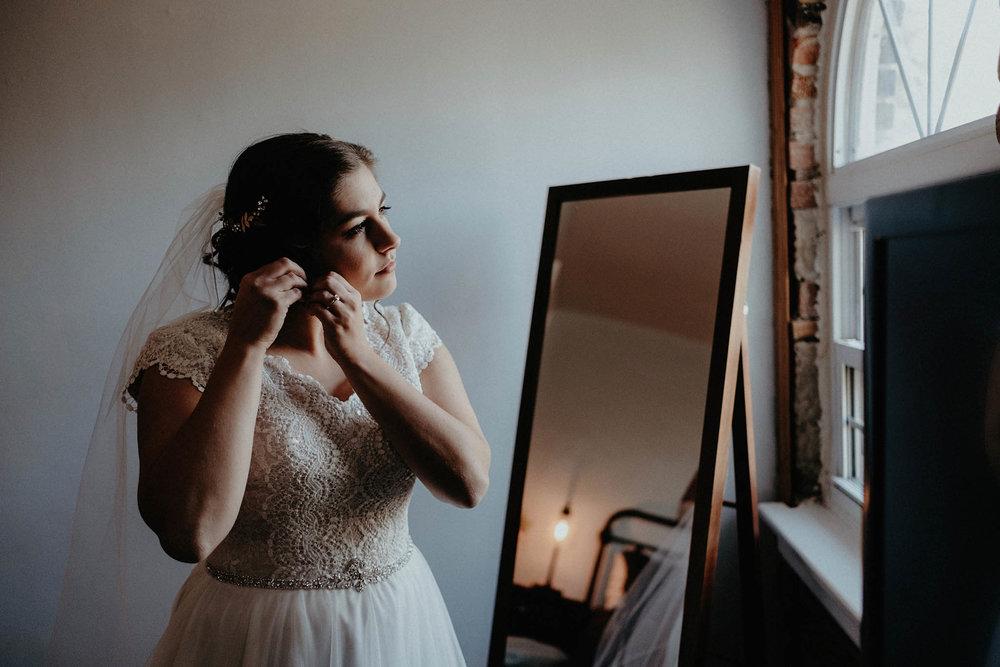 cincinnati warehouse wedding photographer bride putting on earrings
