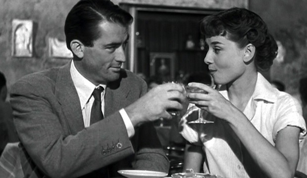 Audrey Hepburn and Gregory Peck drinking champagne at a Roman Cafe in  Roman Holiday.