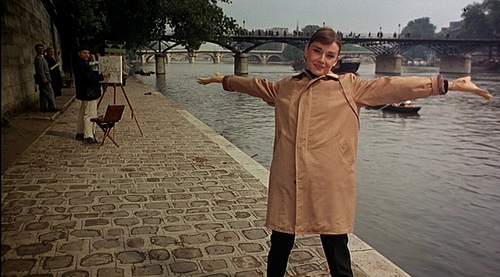 "Hepburn signing ""Bonjour Paris!"" on the River Seine in Funny Face."