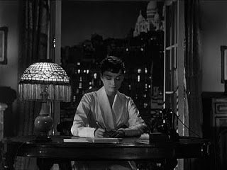 Hepburn's character writing to her father as she begin her journey home from Paris in Sabrina.