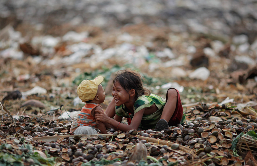 A girl plays with her brother as they search for usable items in a junkyard near the Danyingone station in Yangon's suburbs, on May 16, 2012.(Reuters/Damir Sagolj)