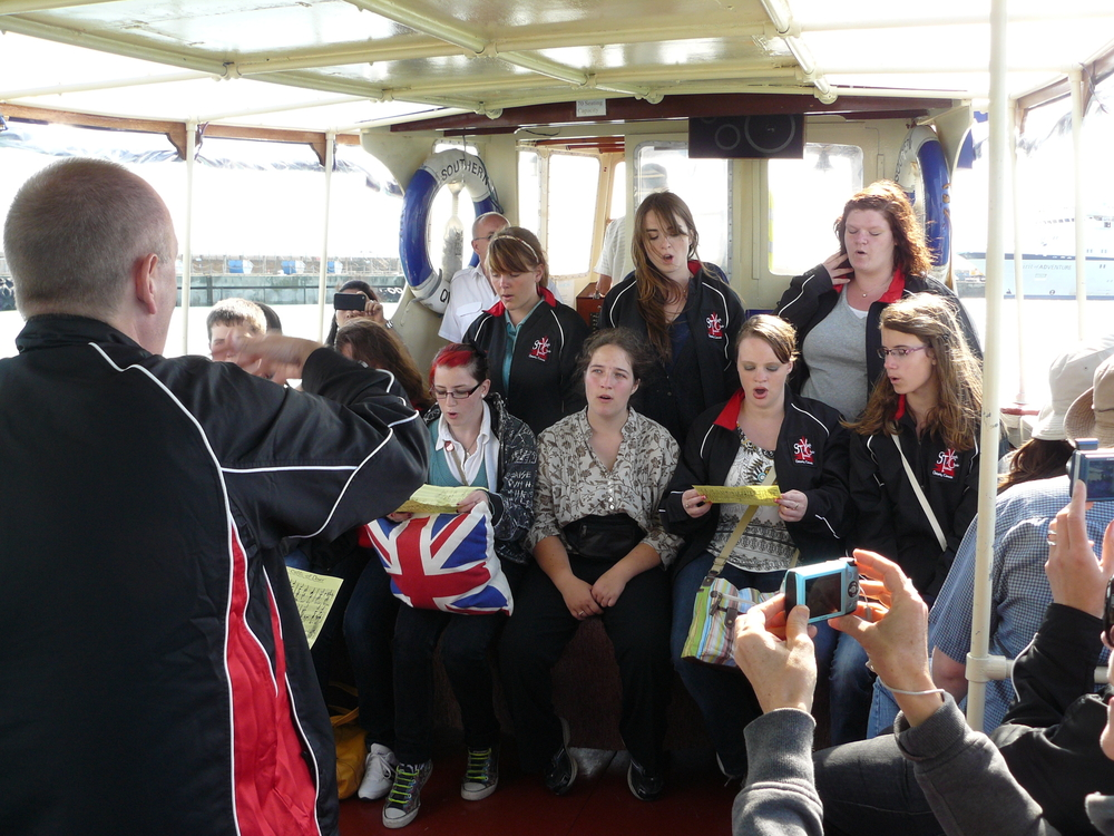 "Graham conducting ""The White Cliffs of Dover"" from our boat ride to see the cliffs."