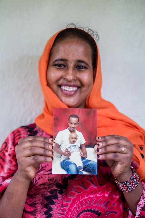 Farhia holding a Photo of Abdifatah and their son Abshir.