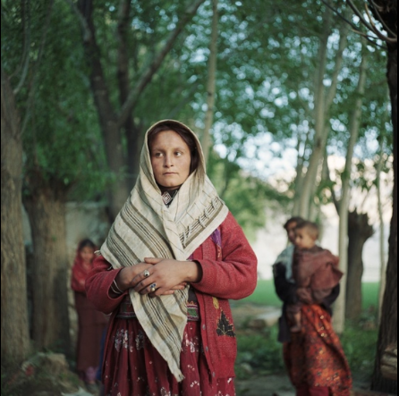 A Wakhi woman stands near her family in the village of Ghaz Khan.