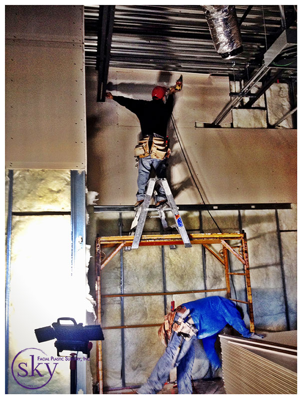 PHOTO: Man on a ladder installs drywall in lobby.