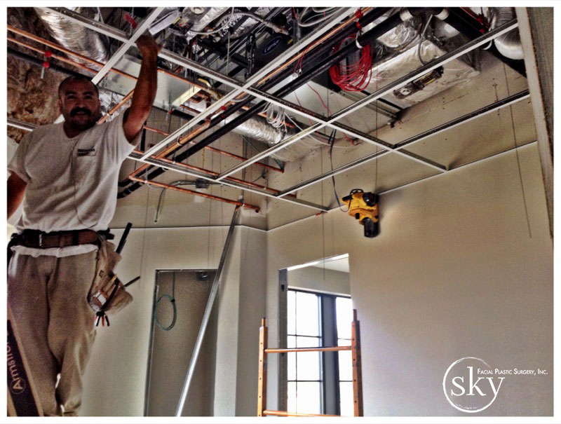 PHOTO: Man installing drop-down ceiling.