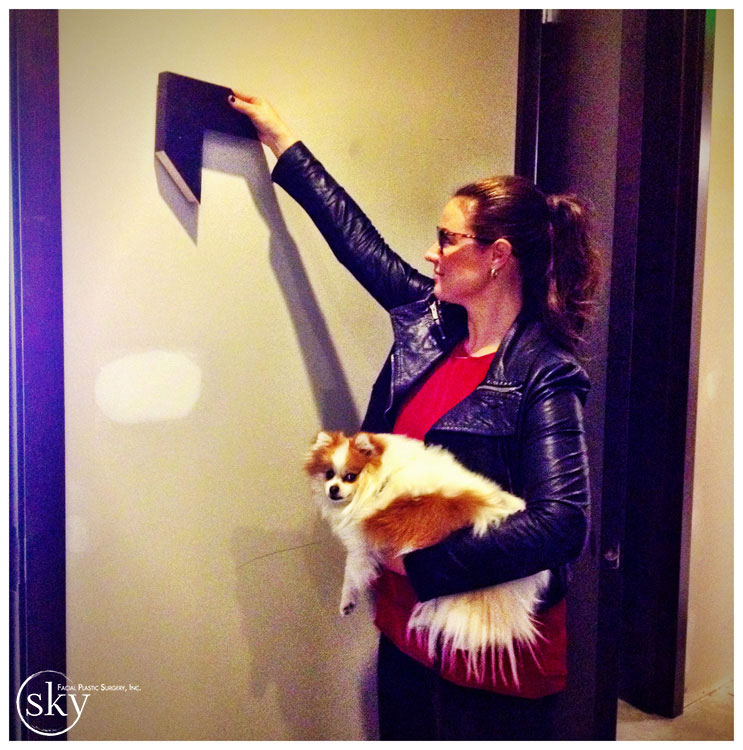 PHOTO: Kelly positions frame against wall, while holding dog.