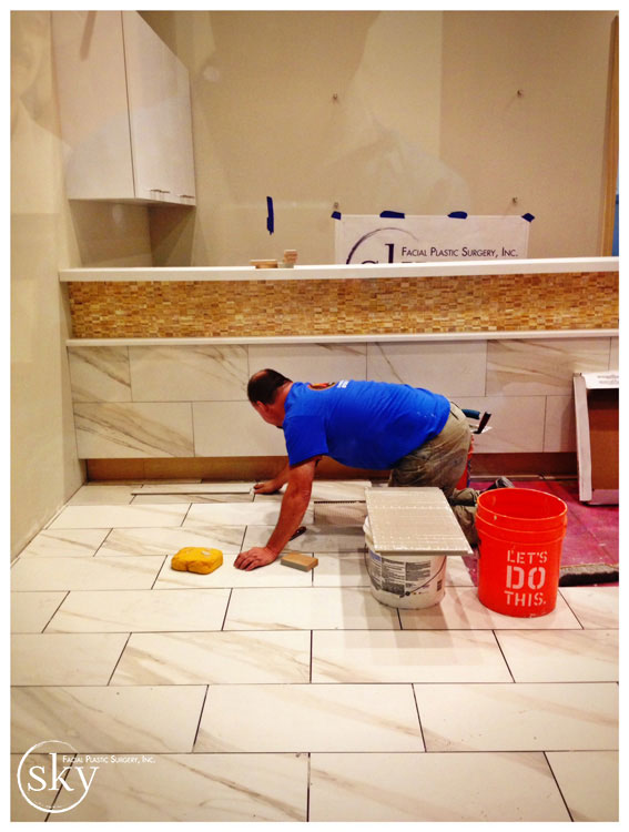PHOTO: Man installing floor in lobby.