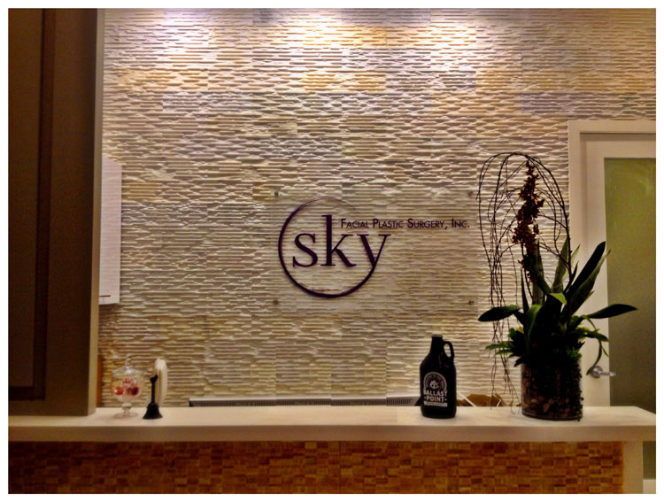 PHOTO: Lobby with logo, tiled wall and plants.