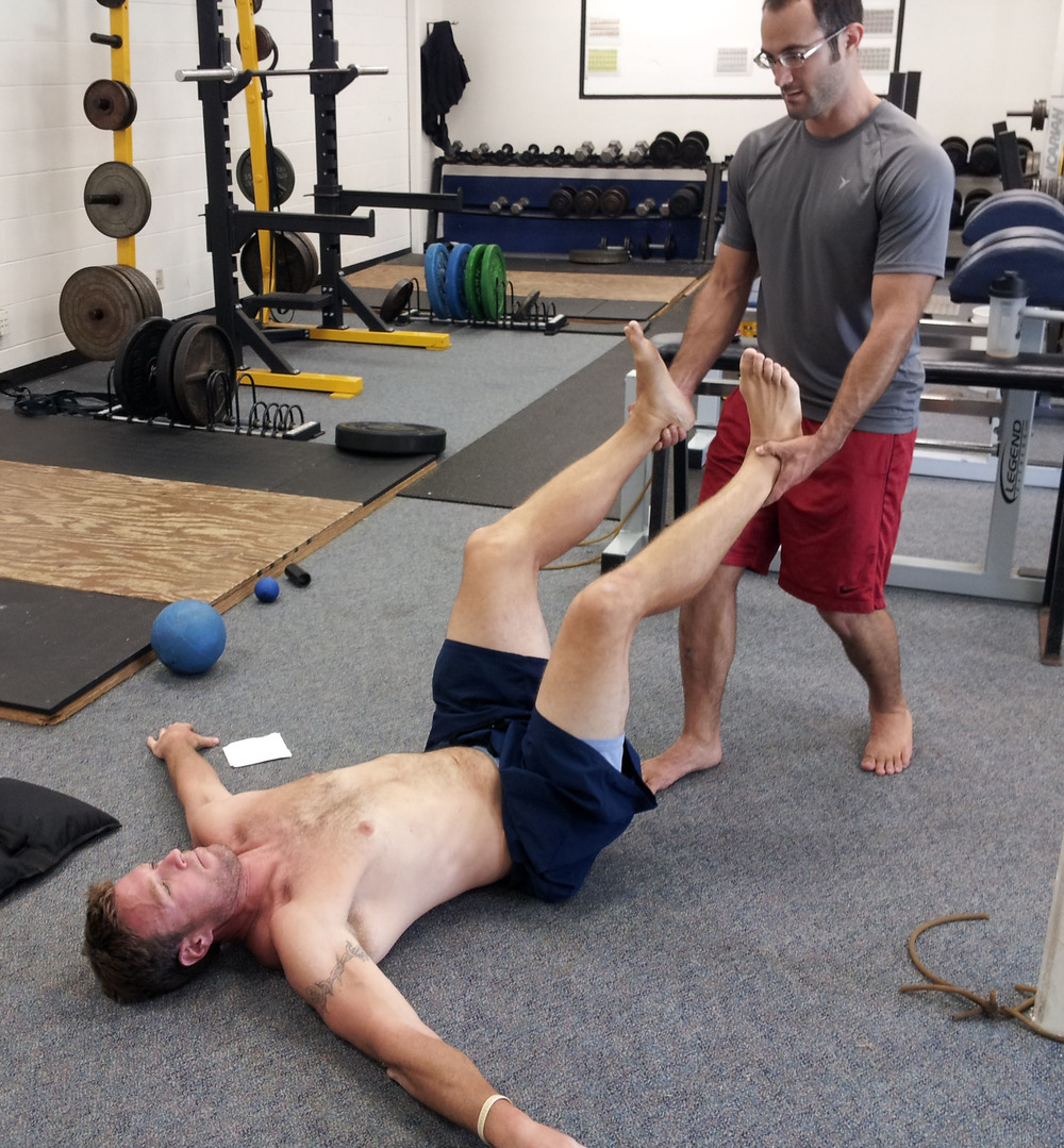 San Diego personal trainer, Brian Tabor, assists with a supine hip flexor activation.