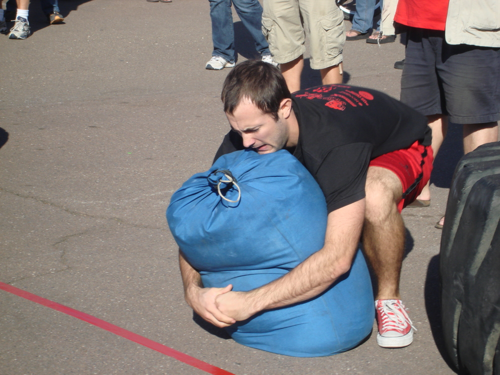 Strongman and San Diego personal trainer, Brian Tabor,  picking up an IronMind sandbag in competition.