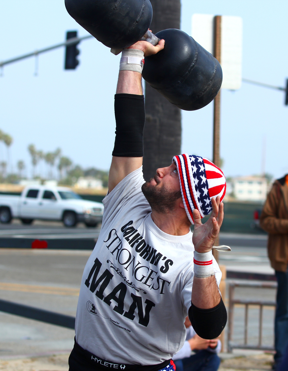 San Diego personal trainer and strongman performs 1 arm dumbbell press