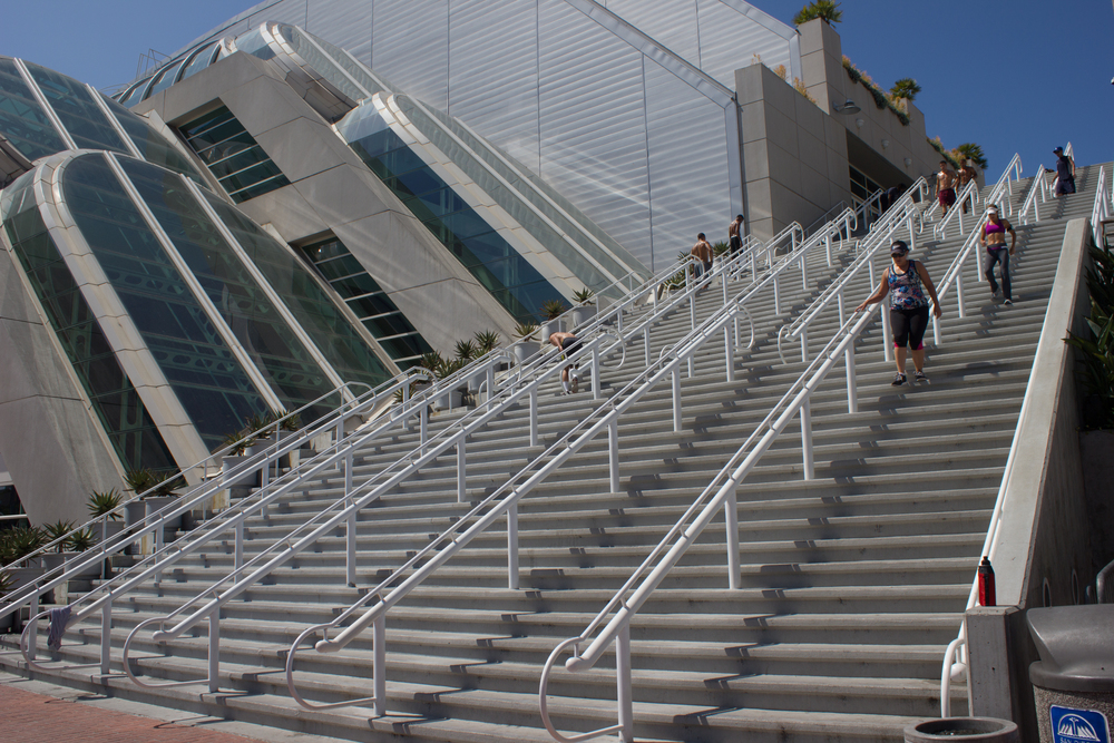 A group of people running the stairs of the San Diego Convention Center. One gentleman apparently puking.