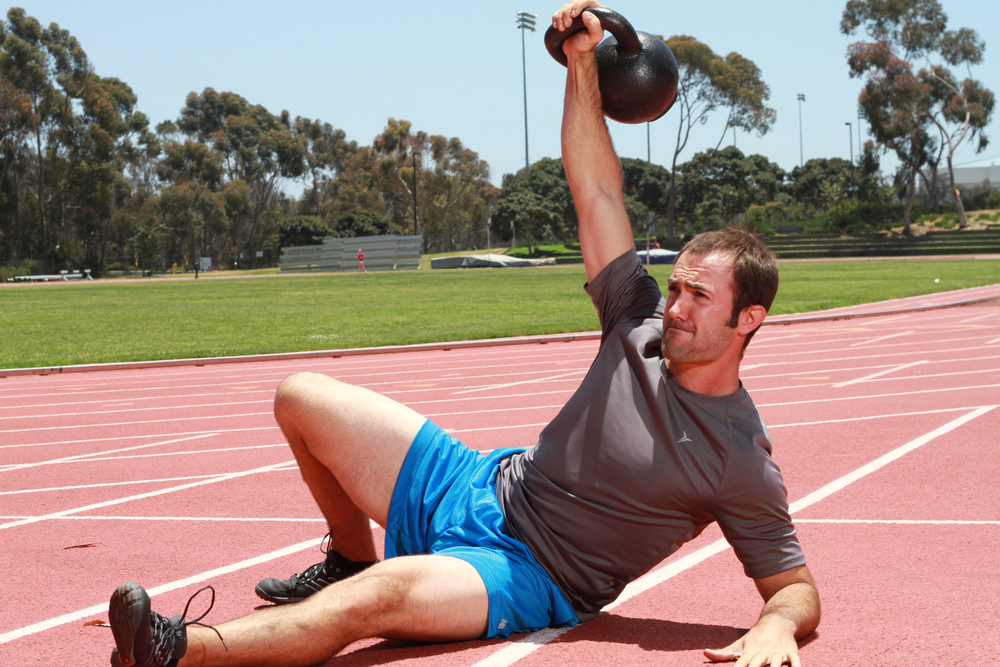 San Diego personal trainer, Brian Tabor, performing a turkish get up at the UCSD track during a workout.