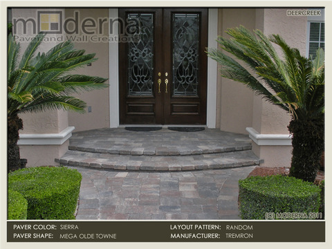 This entryway was created with two slow curving steps made out of pavers with a wide walkway that sweeps out to the columns.