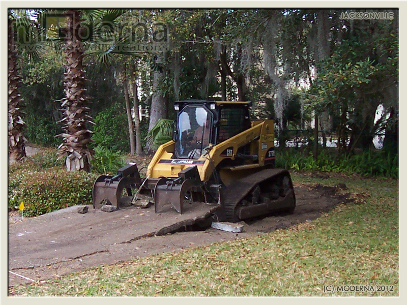 Moderna removing the concrete with a Caterpillar track machine in Jacksonville FL
