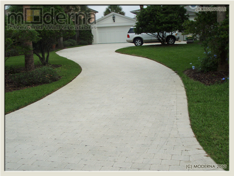 The white brick paver driveway photographed about 1 year after installation by Moderna.