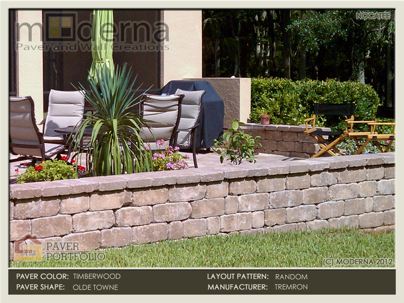 Brick Paver patio and Retaining Wall installation in Nocatee FL. The retaining wall makes up the slope in the yard. Timberwood color.