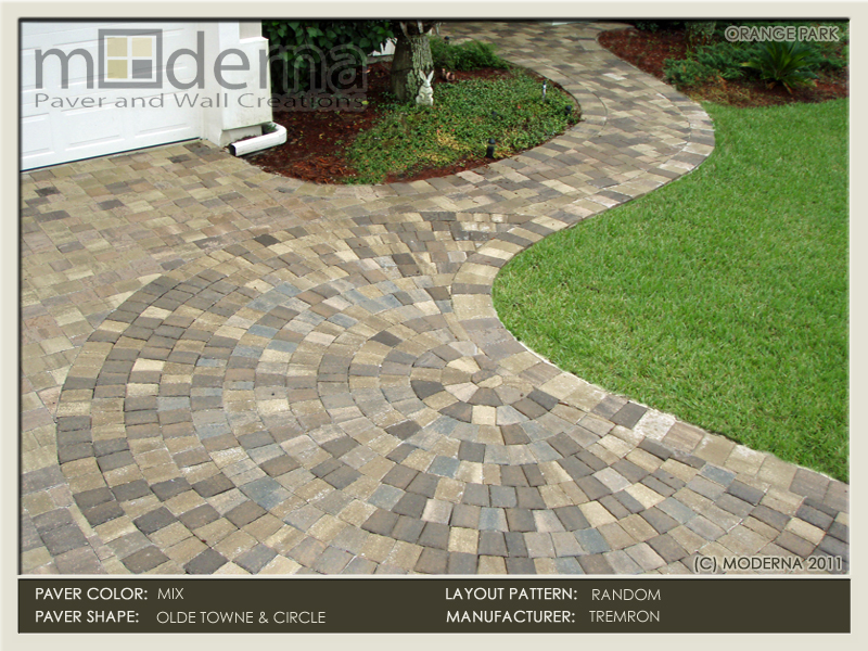 A circular paver pattern makes up the transition from the driveway into the walkway of this Orange Park home. There is a mixture of colors used.