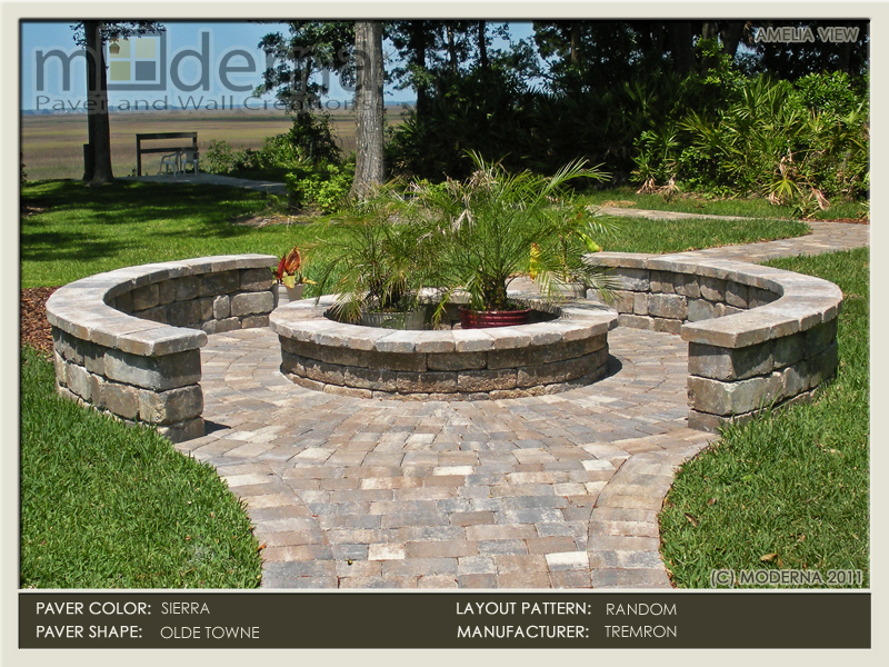 A fire pit with a surrounding seating wall in Jacksonville FL. THe patio inside the seat wall utilizes a circular paver pattern. Sierra color pavers.