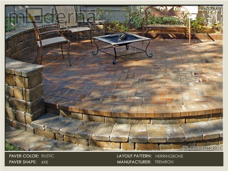 A 4 x 8 brick paving patio with several steps leading to the yard. The pavers are Herringbone pattern and have blended colors of Red and Charcoal.