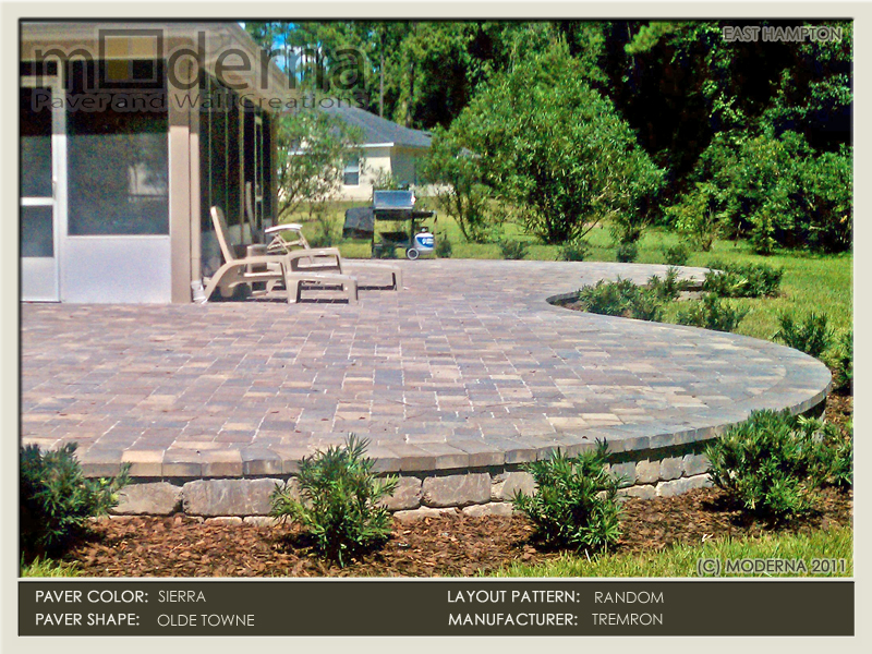 A large paver patio raised by retaining wall surrounded by new landscaping, lighting, and irrigation re-work. The pavers and wall are Sierra color.