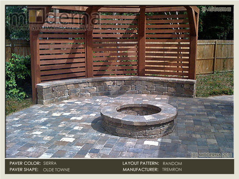 "This fire pit and seat wall is anchored by a three sided ""curved"" pergola. The fire pit, pavers, cap, and seat wall are Sierra color."