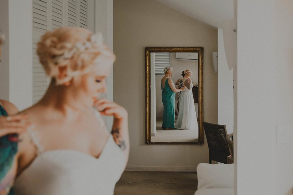 Alternative inked bride with pink hair getting ready with bridesmaids
