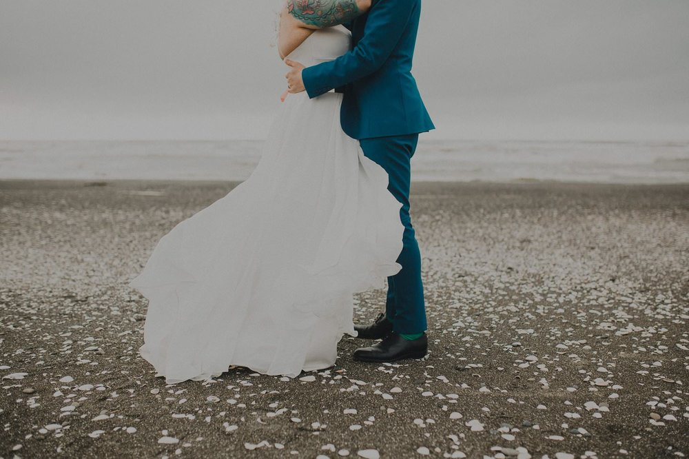 Sally Eagle Marilyn Gown; Bride and groom embrace on the beach