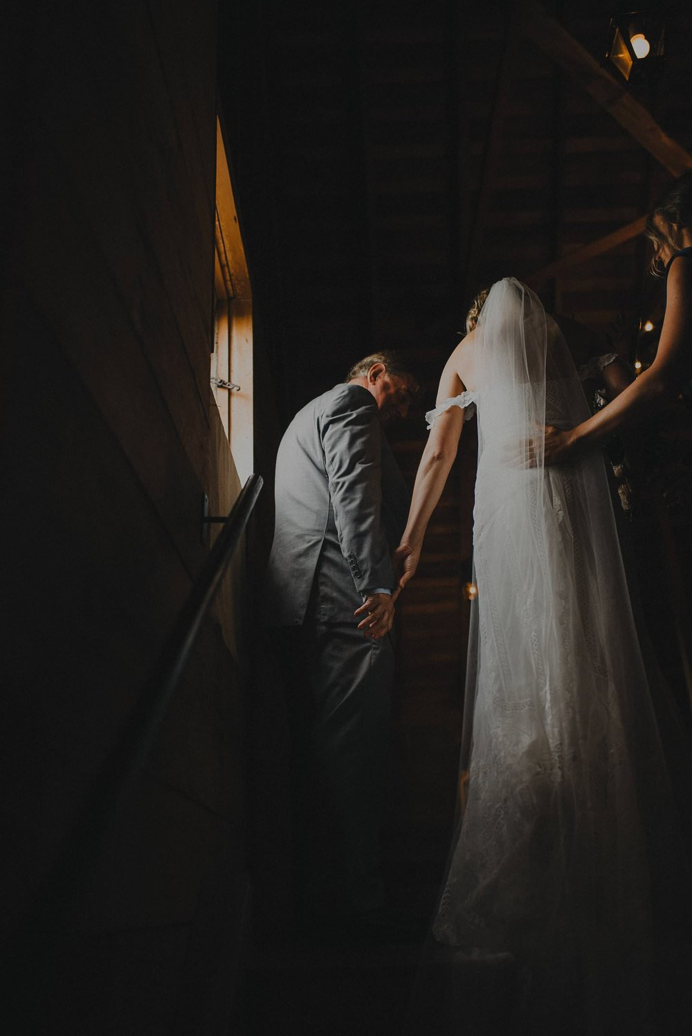 Dramatic shot of bride and her father walking down the aisle