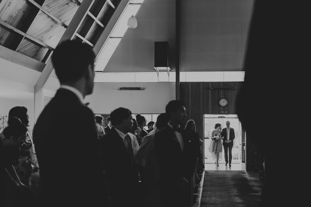 Dramatic shot of bride walking down the aisle