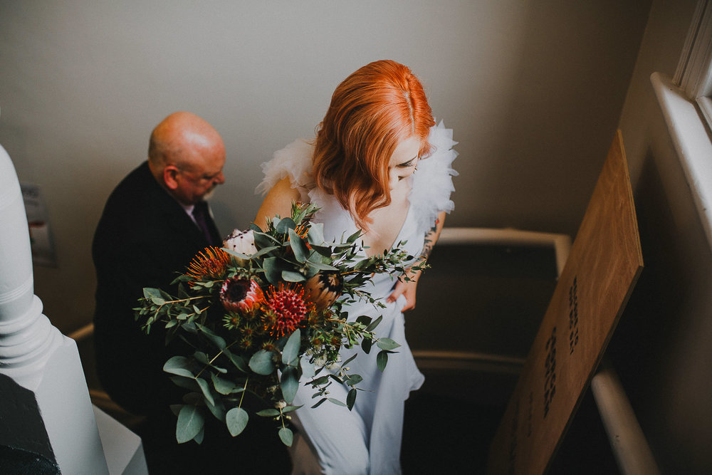 Redhaired bride walking up stairs with rustic hand tied bouquet