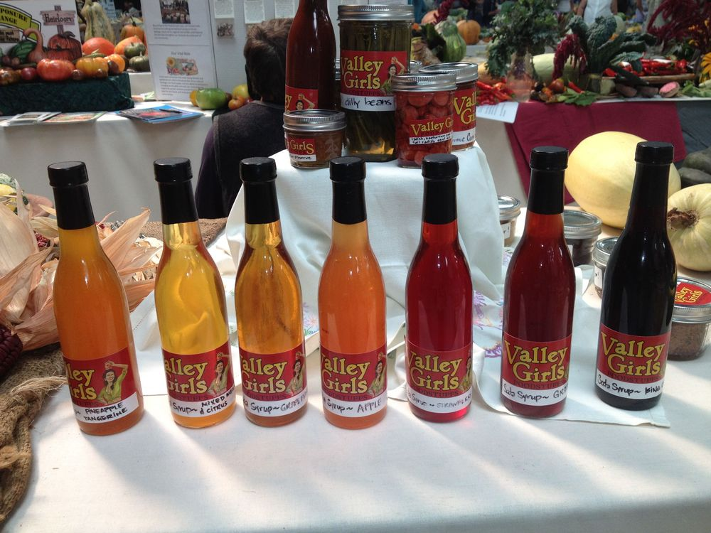 Our products on display in the exposition hall, featuring our colorful real fruit soda syrups in the forefront.
