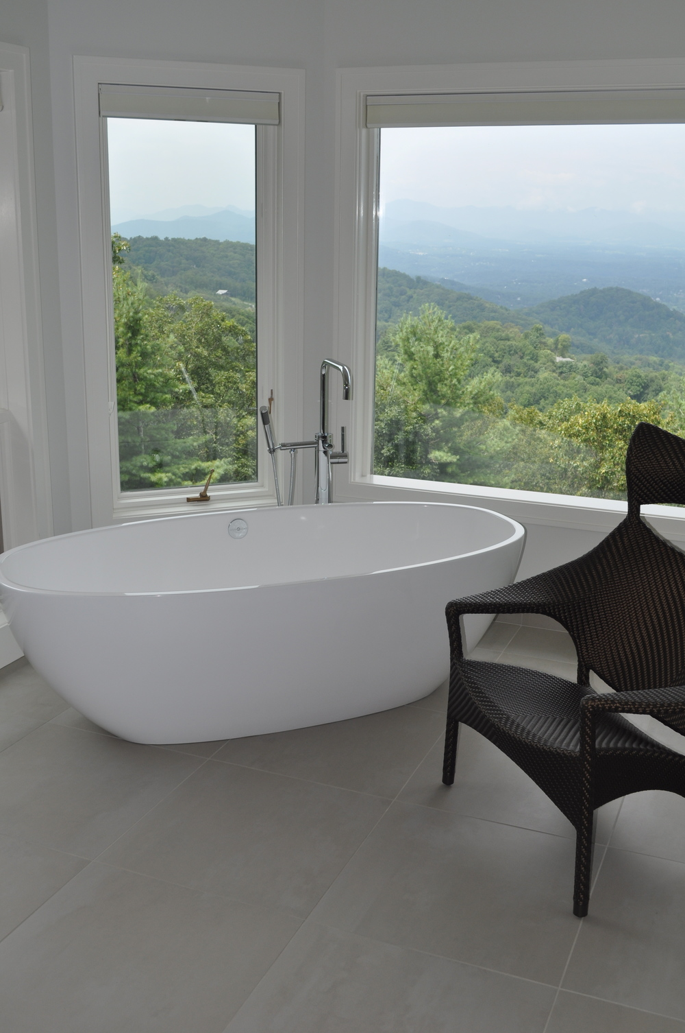 "Boone/Jamison Residence. Beautiful freestanding tub with amazing views set atop 24""x24"" porcelain tile. This bathroom has a very modern clean look"