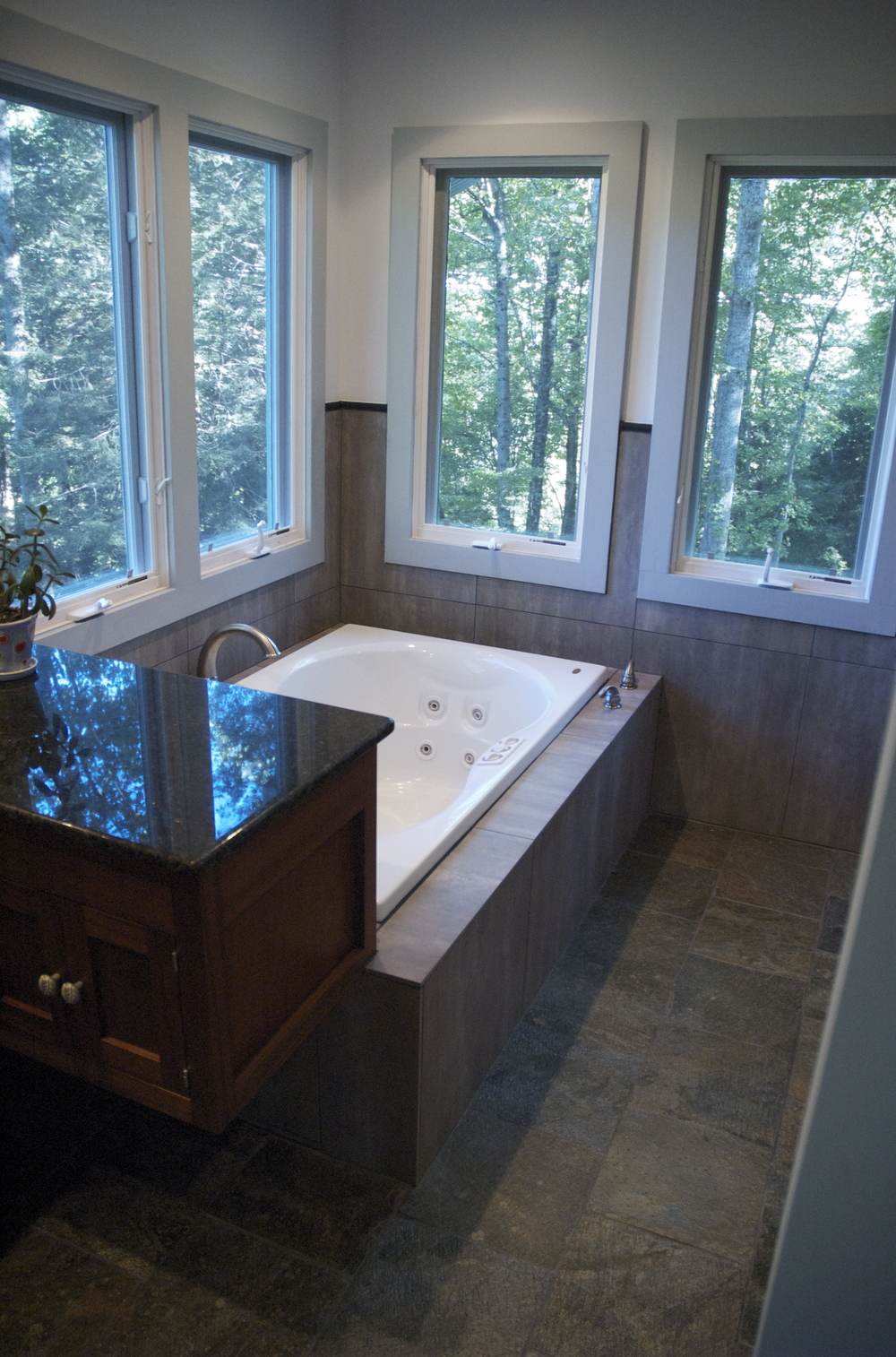 Wheeler Residence. This jet tub is surrounded by a very modern smooth porcelain tile that is contrasted as well as complimented by the natural slate tile floor. This bathroom is an oasis in a rustic setting.