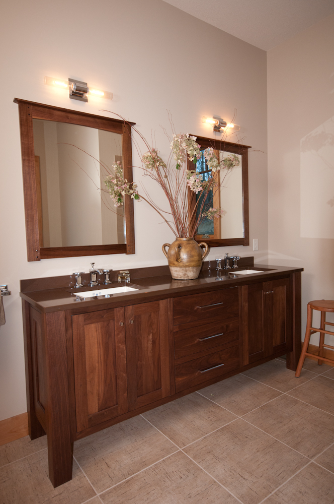"Custom walnut mirrors crafted to match walnut vanity that sits atop 24""x24"" porcelain tile."