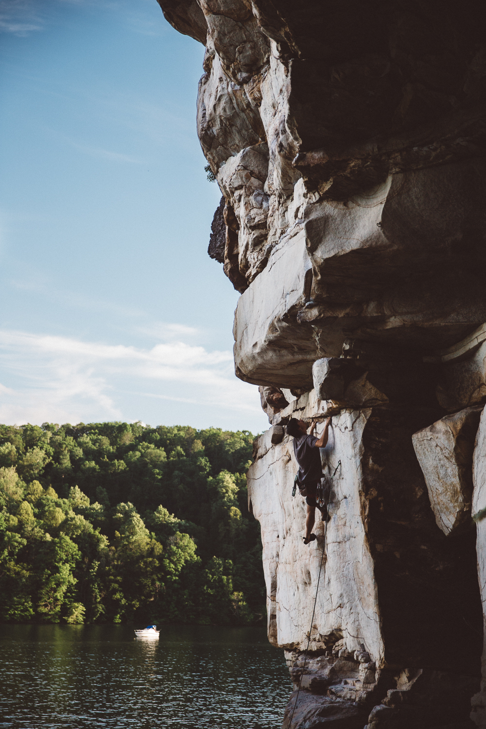 Alex Lin climbing a 5.12a route over Summerville Lake at the New River Gorge.
