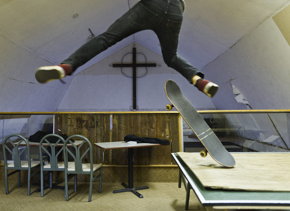 A Skateboarder launches off a ping pong table at the Crossroads Youth Center in Spencerport, NY after worship services. The Youth center provides a combination of Christian education and skateboarding, with a barn that has been converted to an indoor, outdoor extreme sports park.