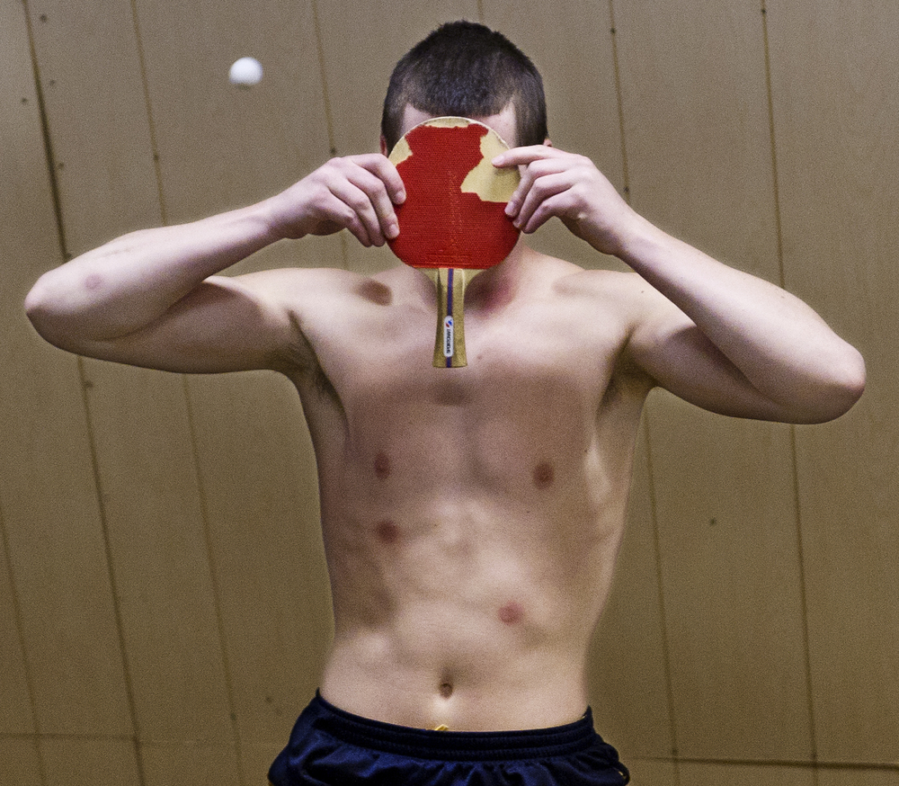 "A skater shields his face from an incoming ping pong ball during a game of ""sting pong"" at the Youth Center, after some visibly successful hits."