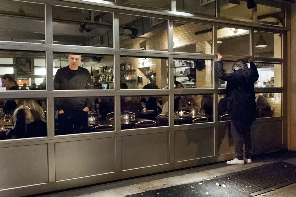 A demonstrator presses himself up against the window of an upscale restaurant in Lower Manhattan.