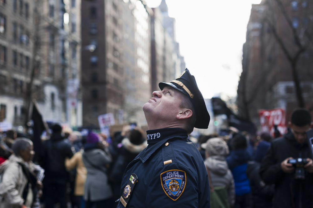 "an NYPD officer looks up at the circling news helicopters before a ""Millions March"" demonstration on December 13th, 2014 that drew more than 60,000."
