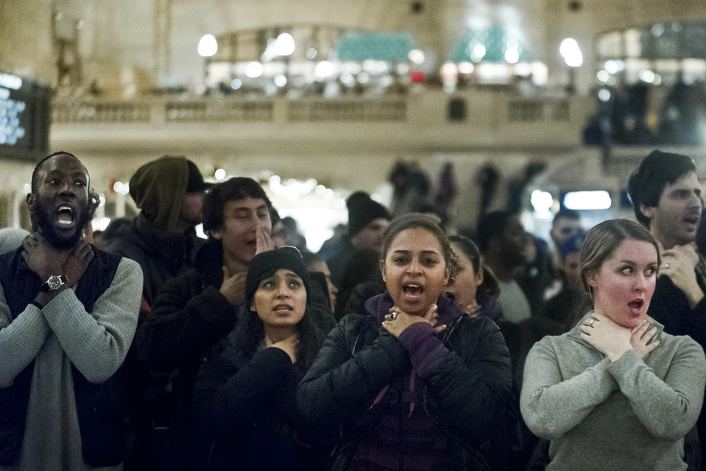 "Protestors participate in a ""choke-in"" while chanting ""I can't breathe"" at Grand Central Terminal in protest of the grand jury's failure to indict officer Daniel Pantalero in the death of Eric Garner."