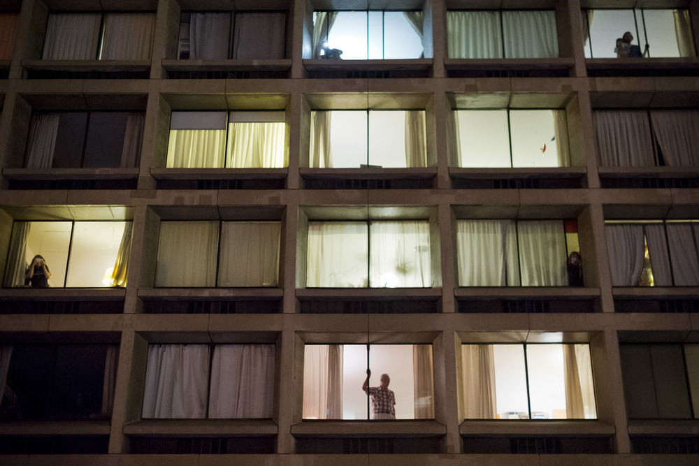 Protest onlookers fill the South-facing windows of an apartment complex on Houston street,
