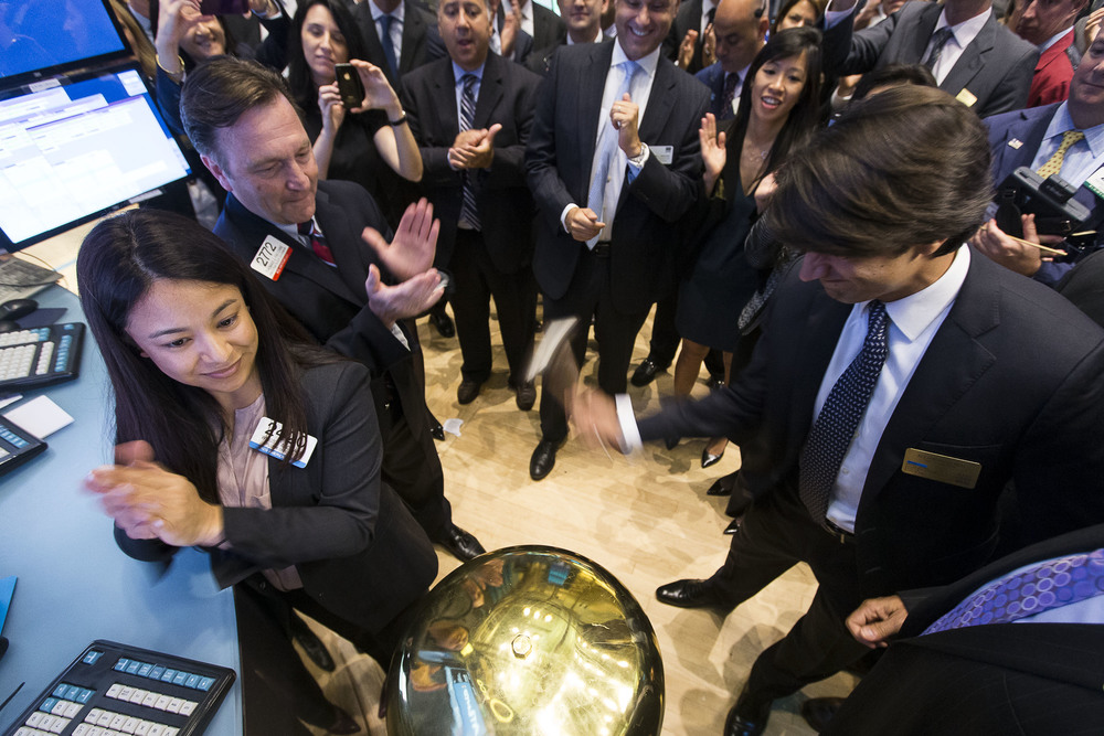 A CEO forcefully rings the first trade bell, signifying the official opening of his company's stock.