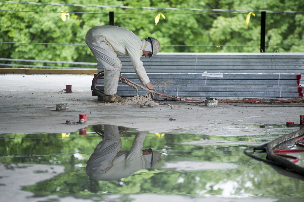 A worker prepares a fireproofing hose. Work continues through the rain at 55-65 Campus Avenue.