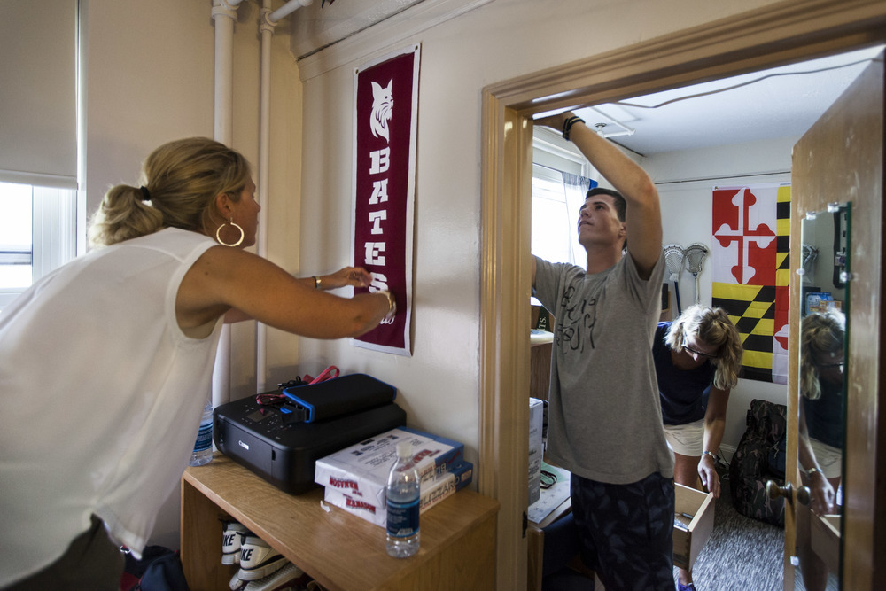 Lisa Legowski hangs a newly purchased Bates banner for her son Justin Legowski '19 of Farmington, Connecticut, while his roommate Eli Nixon '19 of Eliot, Maine, decorates his section of the room on Move In Day.