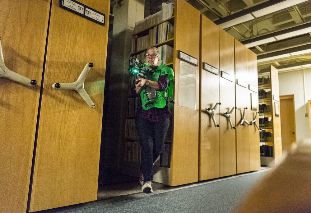Assistant Vice President of Dining Christine Schwartz springs out from her hiding spot as students, faculty and staff came together to play Lazertag, darting and dodging between the many volumes of Ladd Library.