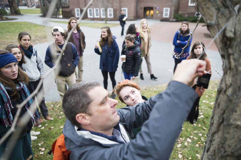 Rebecca Leloudis '16 of Chapel Hill, NC watches as Professor Brett Huggett hangs a tree tag. Students in Brett Huggett's class complete their semester long project of mapping and tagging all of the trees on the Historic Quad.